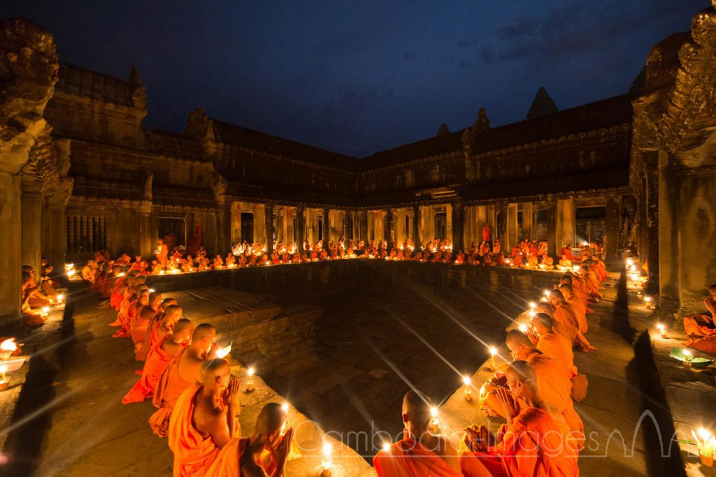 Monks meditate under candle light during a buddhist ceremony, Angkor Wat, Siem Reap, Cambodia.